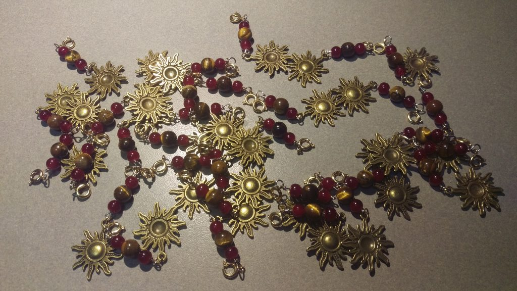 Brass Sun charm with red glass and tiger's eye beads